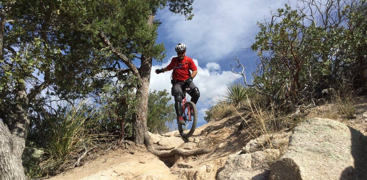 Picture of unicyclist riding down a rock